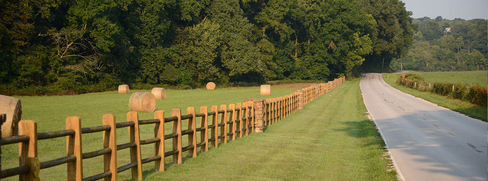 Country road with fence and hay bales.